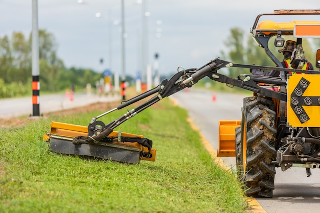 Tractor with a mechanical mower mowing grass on the side of the asphalt road Premium Photo