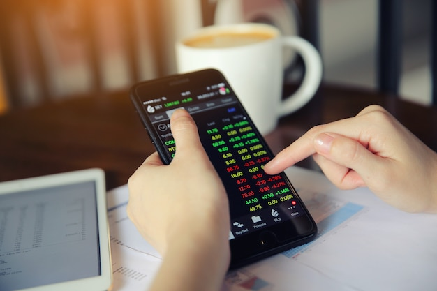 Trading online on smartphone with bussiness woman hand Premium Photo