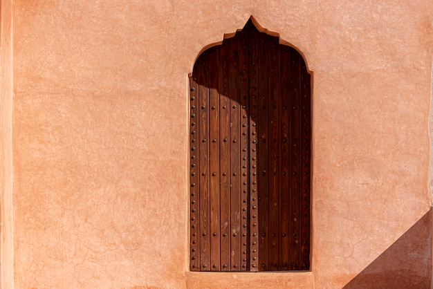 Traditional arabian architecture, muslim style wooden door and red clay wall Premium Photo