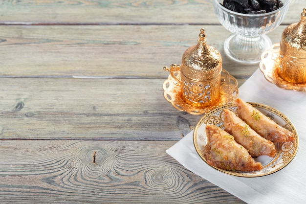 Traditional arabic dessert baklava with cashew, walnuts and cardamom with an eucalyptus branch on a wooden table Premium Photo