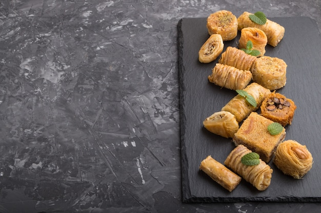 Traditional arabic sweets on a black slate board on a black concrete background. side view, copy space. Premium Photo