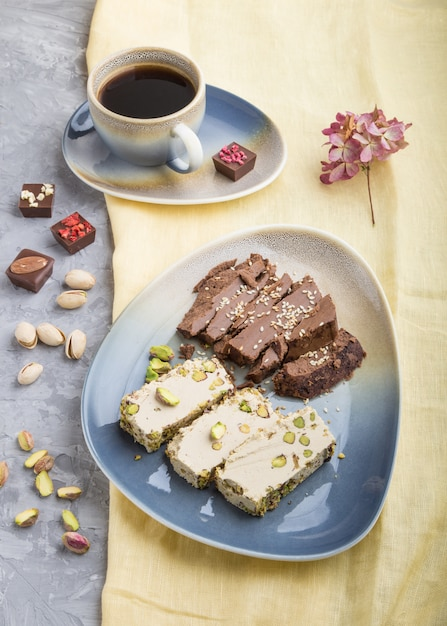 Traditional arabic sweets sesame halva with chocolate and pistachio and a cup of coffee. side view, close up. Premium Photo