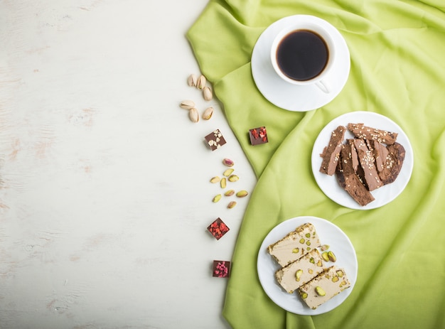 Traditional arabic sweets sesame halva with chocolate and pistachio and a cup of coffee. top view Premium Photo
