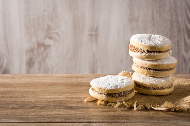 Traditional argentinian alfajores with dulce de leche and sugar on wooden table, copy space Premium Photo