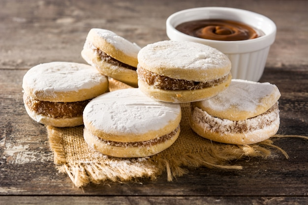 Traditional argentinian alfajores with dulce de leche and sugar on wooden table Premium Photo