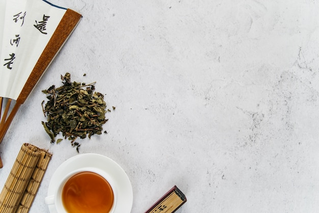 Traditional asian fan with herbal tea and rolled up placemat on concrete backdrop Premium Photo