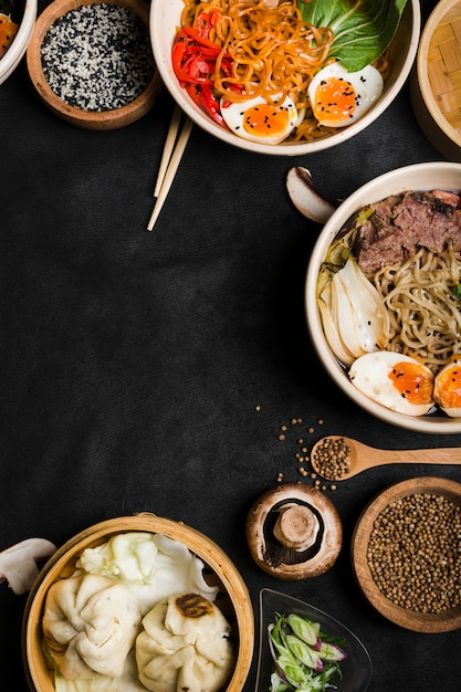 Traditional asian noodles bowls with steamed dumplings on black backdrop Free Photo