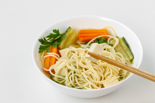 Traditional asian soup with tofu cheese, noodles, carrots and zucchini. this dish usually contains bouillon and vegetables Premium Photo