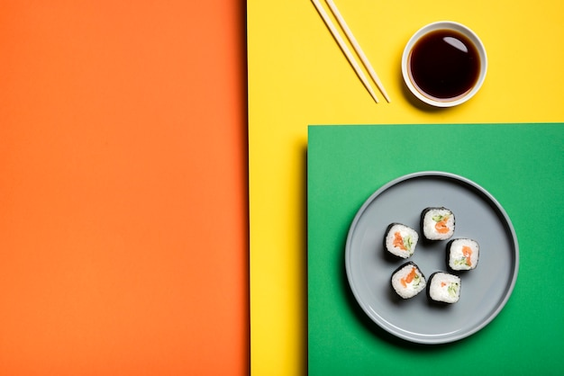 Traditional asian sushi rolls on colourful background Free Photo