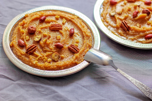 Traditional azerbaijan, indian, turkish sweet dessert halvah with nuts on top Free Photo