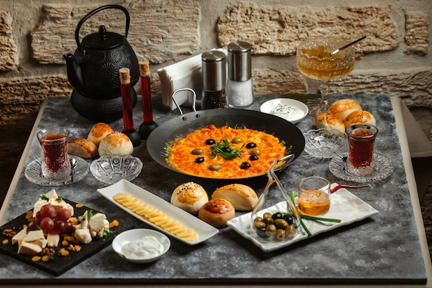 Traditional azerbaijani breakfast with egg and tomato dish, tea, cheese and butter Free Photo