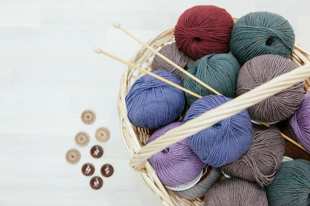 Traditional basket full with colorful wood of yarns, knitting needles and a variety of buttons Premium Photo