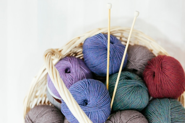 Traditional basket with a variety of wood of yarns and needles to knit Premium Photo