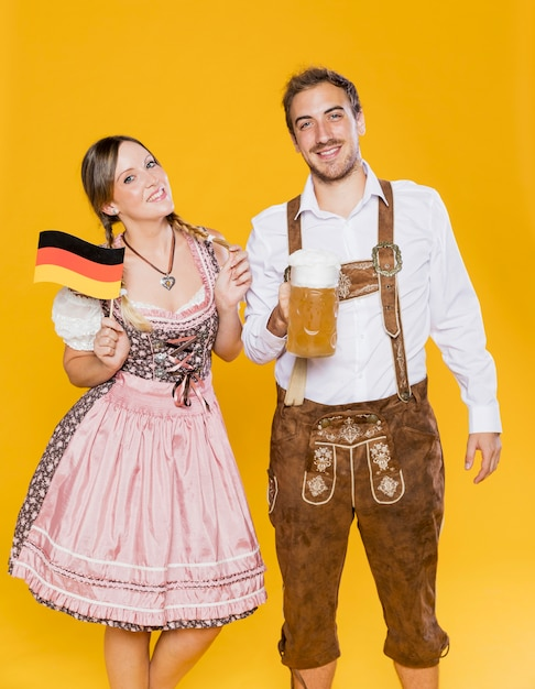 Traditional bavarian couple with flag and beer Free Photo