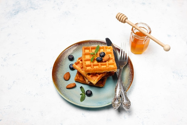 Traditional belgian waffles with fresh berries and honey on grey concrete surface. Free Photo