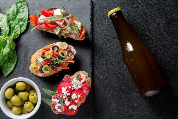 Традиционная брускетта. итальянские закуски с хамоном, колбасой, оливками, творогом, рукколой и помидорами на черном фоне Premium Фотографии