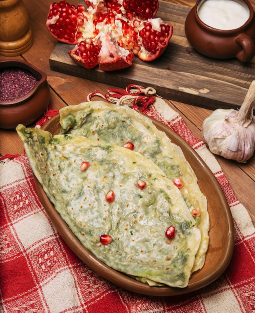 Traditional caucasian vegetable gutab, kutab, gozleme with sumakh, granate seeds and yogurt in wooden plate. Free Photo