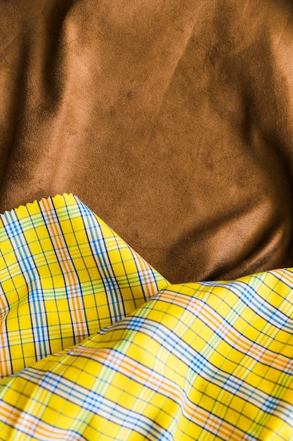Traditional checkered fabric texture on brown drape textile Free Photo