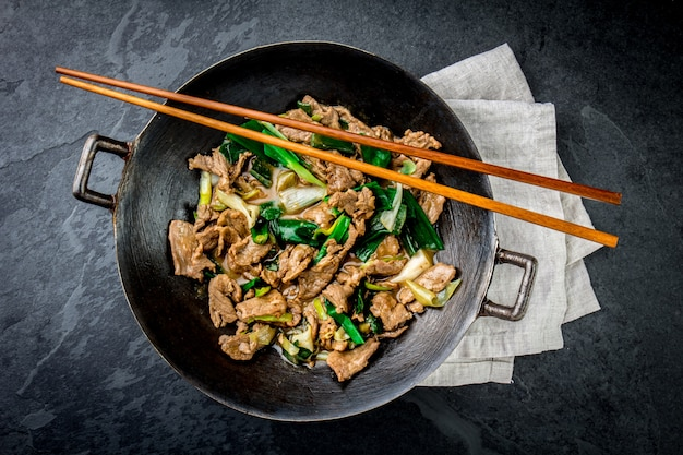 Traditional chinese mongolian beef stir fry in chinese cast iron wok with cooking chopsticks Premium Photo