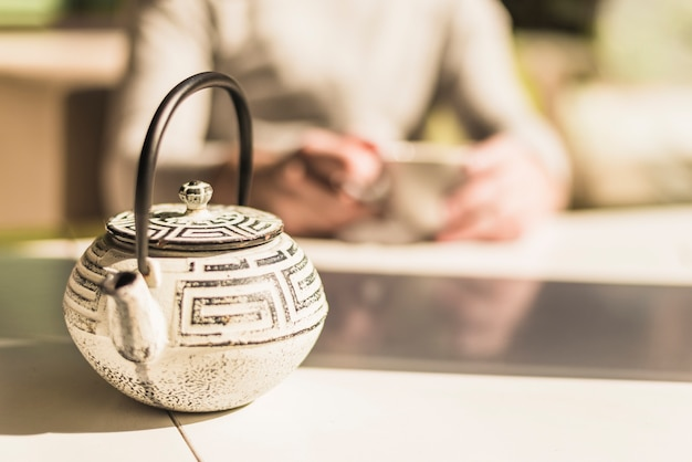 Traditional chinese teapot with a lid on table in the sunlight Free Photo