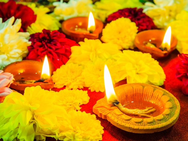Традиционные глиняные лампы diya, освещенные цветами для празднования фестиваля дивали Premium Фотографии