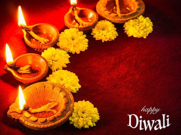 Традиционные глиняные лампы diya освещены цветами для празднования фестиваля дивали. Premium Фотографии