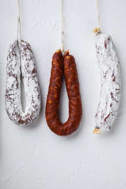 Traditional dry cured sausages meat hanging on white surface. Premium Photo