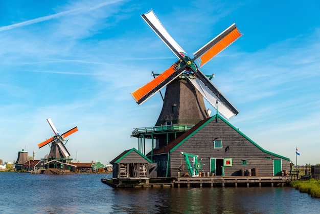 Traditional dutch windmills located by the river zaan, in zaanse schans, netherlands. Premium Photo