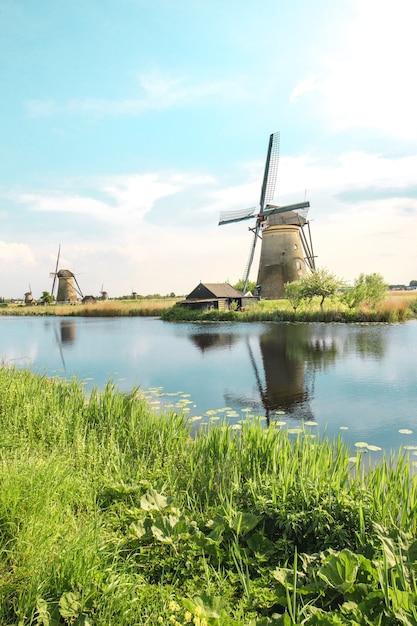 手前に緑の草がある伝統的なオランダの風車 無料写真