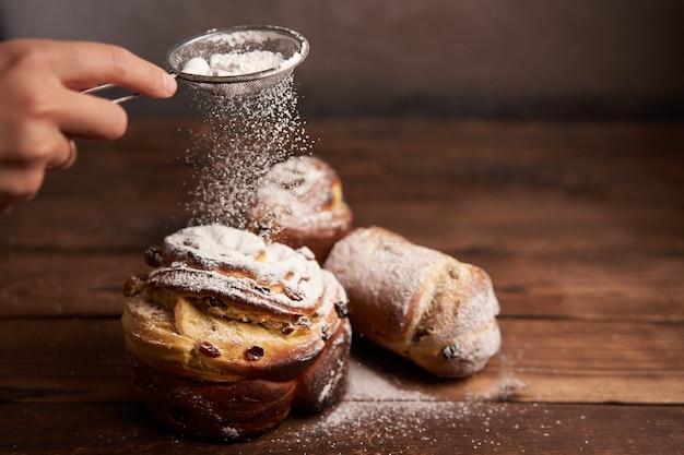 伝統的なイースターケーキクラフィンは、暗い背景に木製のテーブルの上に立っています。コピースペースのある春休みパン料理人に粉砂糖をまぶす Premium写真