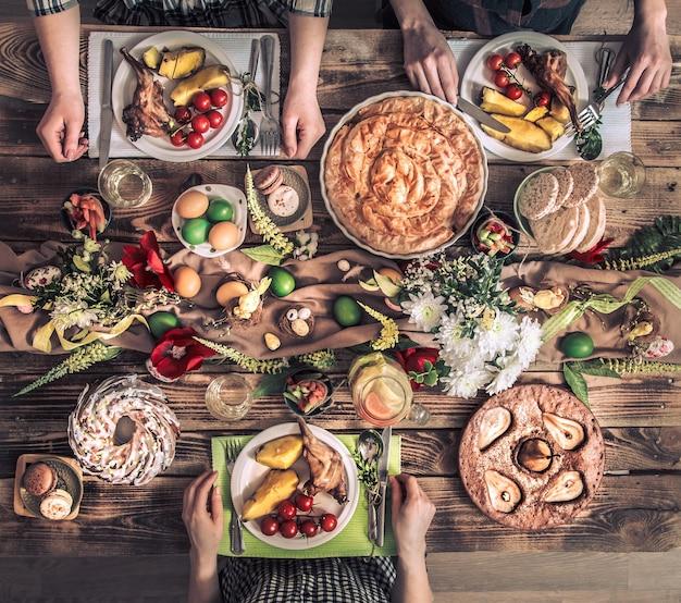 伝統的なイースターのお祝い、イースターホリデーパーティー。休日の友人やウサギの肉、野菜、パイ、卵、上面とお祝いテーブルで家族。友達の手が一緒に食べたり飲んだりします。 無料写真
