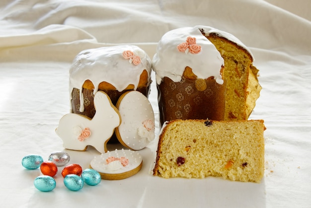 Traditional easter, sweet bread decorated meringue and blue candy cane shape eggs on plate Premium Photo