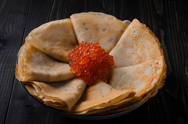 Traditional festive dish  thin pancakes with red caviar. Premium Photo