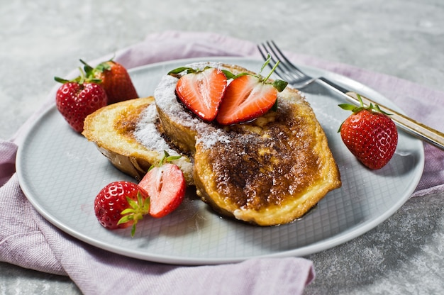 Traditional french toast with strawberries on . Premium Photo