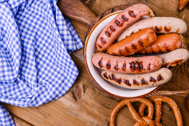 Традиционные немецкие колбаски и кондитерские брезели для пивного фестиваля. дерево и декор. вид сверху Premium Фотографии