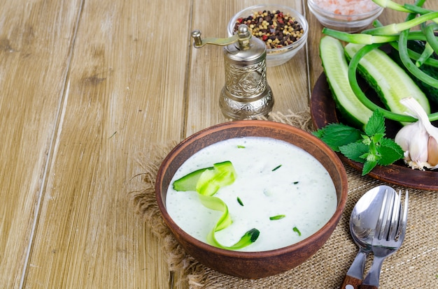 Traditional greek dip sauce or dressing tzatziki prepared with grated cucumber, yogurt, olive oil and fresh dill on wooden table in ceramic bowl. Premium Photo
