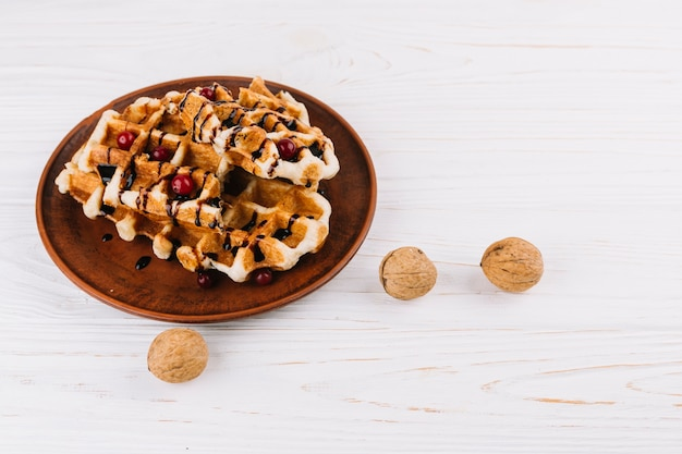 Traditional homemade belgian waffles with fresh berries; syrup and walnuts Free Photo