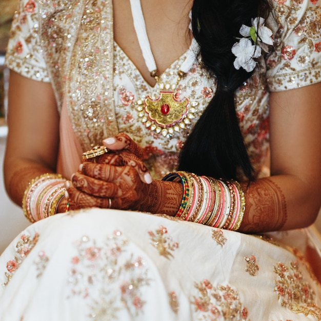 Traditional indian attire and bangles and the crossed hands Free Photo
