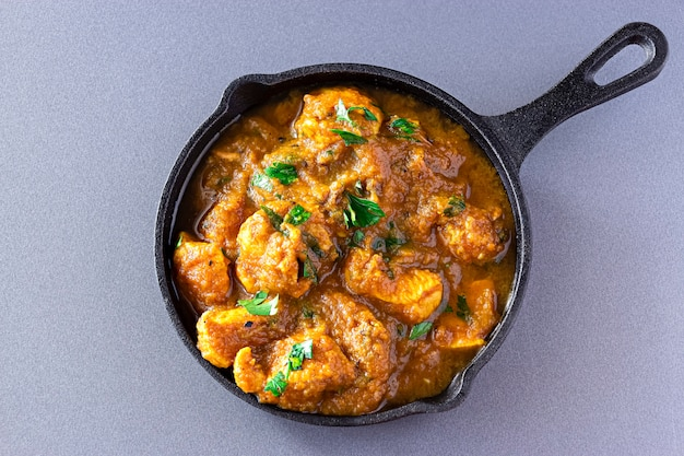Traditional indian butter chicken curry and lemon served iron-cast. top view. traditional world cuisine. Premium Photo