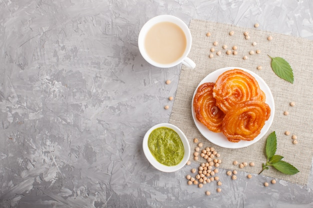 Traditional indian candy jalebi in white plate with mint chutney on a gray concrete copyspace. top view. Premium Photo