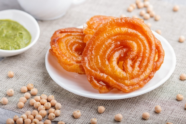 Traditional indian candy jalebi in white plate with mint chutney Premium Photo