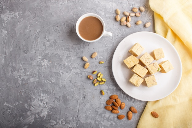 Traditional indian candy soan papdi in white plate with almond and pistache on a gray concrete. Premium Photo