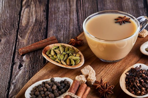 Premium Photo | Traditional indian drink - masala tea with spices.  cinnamon, cardamom, anise, sugar, cloves, pepper on a dark wooden surface.
