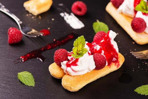 Traditional italian dessert - tiramisu cake with raspberry and mint on black stone background. Premium Photo