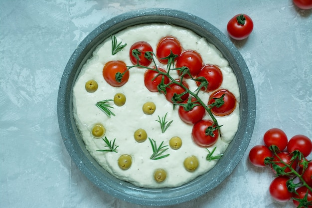Traditional italian focaccia with tomatoes, olives and rosemary Premium Photo