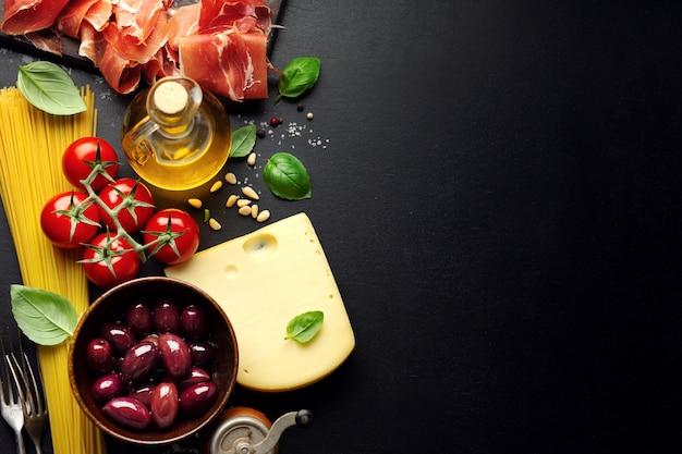 スパゲッティトマトチーズオリーブと暗い背景に油と伝統的なイタリア料理の背景。 Premium写真