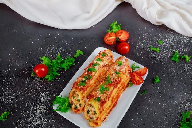 Традиционная итальянская паста ронделли с томатным соусом на деревенском фоне Premium Фотографии