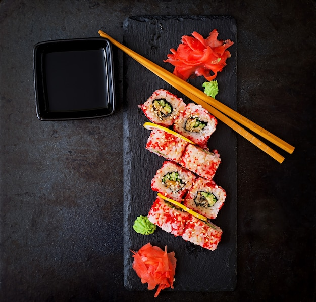 Traditional japanese food - sushi, rolls and sauce on a black background. top view Premium Photo