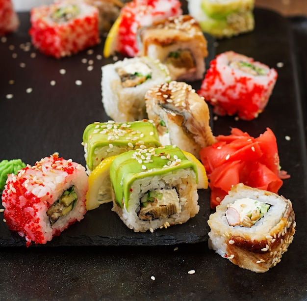 Traditional japanese food - sushi, rolls and sauce on a black background. Premium Photo