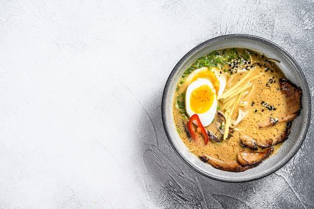 Традиционный японский суп рамен с мясным бульоном, азиатской лапшой, водорослями, нарезанной свининой, яйцами. белый фон Premium Фотографии